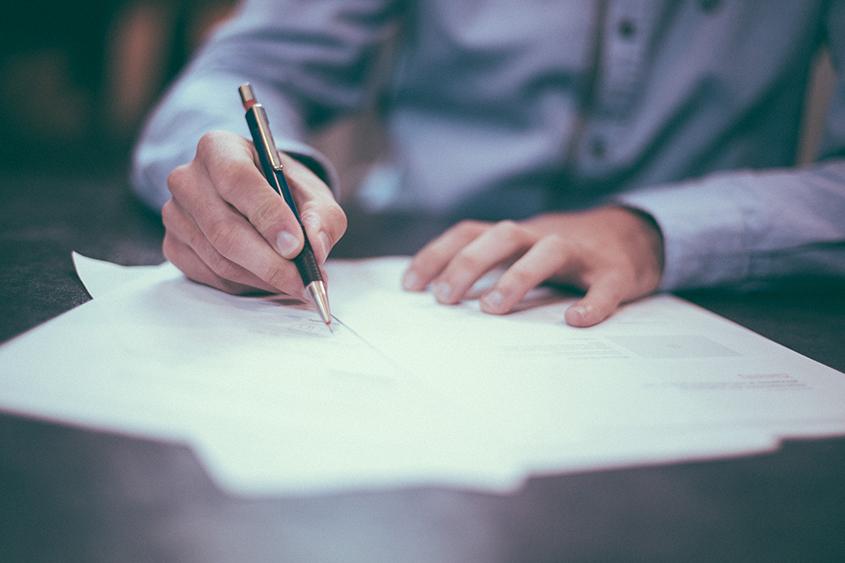 Hand schreibt Notiz auf Zettel